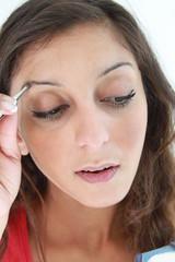 Junge Frau beim Augenbrauen zupfen