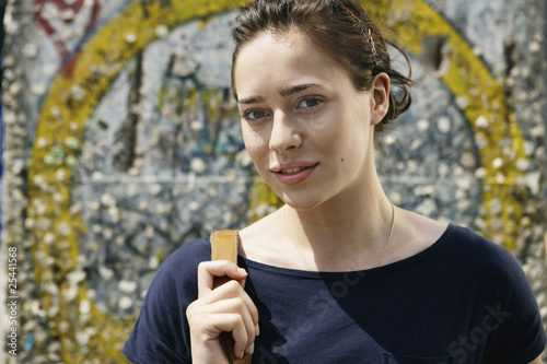 germany, berlin, young woman standing in front of wall with graffiti, portrait, close-up