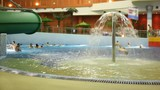 People bathe in pool with a fountain in indoor water park