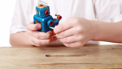 boy turns with winder clockwork robot, it marches forward