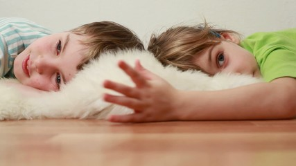 boy and girl  lie on floor on shaggy shawl and are kept in hands