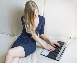 Young woman using laptop on the couch