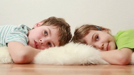 boy and little girl  lie on wooden floor on shaggy carpet