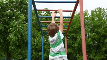 boy in shirt climbs down wall bars like monkey on playground