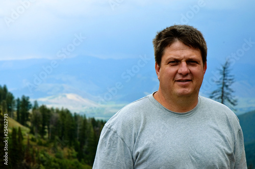 Ordinary guy outdoors with mountains and trees in background