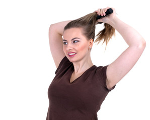 combing woman with long hair in brown blouse