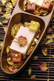 Wooden bowl of soap with withered petals on bamboo mat poster