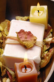 Wooden bowl of soap with withered petals and burning candle poster