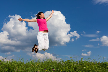 Woman jumping, running against blue sky