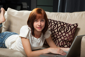 Young female at home lying on the sofa with laptop computer