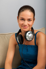 Young female sitting on the sofa with headphones on her neck