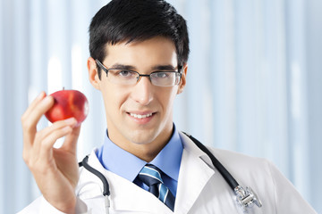 Happy smiling doctor with apple, at office