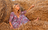 Beautiful blond woman in a haystack