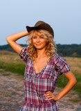 Beautiful blond yougn woman in a cowboy hat and dress