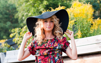 Beautiful blond young woman in the big hat