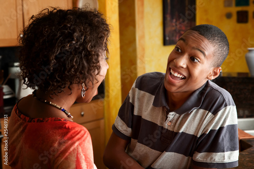 African-American woman and teen laugh in kitchen
