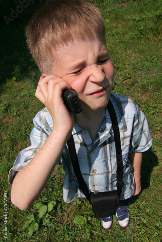 Young boy is phoning very grumpy