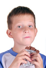 Young boy eat bar of chocolate