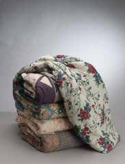 stack of folded blankets on gray background