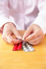 薬を手に取る高齢者