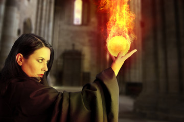 Young beautiful girl with fire sphere, sorcerer