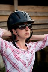 Costa Rican tourist putting on equestrian helmet