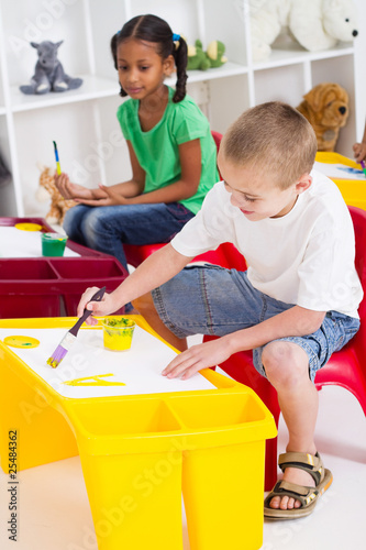 happy young kids painting in classroom