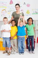 happy preschool boy holding trophy with classmates