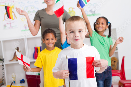 happy little french boy with diverse classmates in background