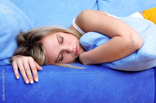 Young woman sleeping atpillows in blue sofa