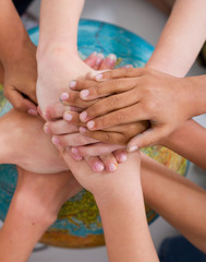 diverse kids hand on globe