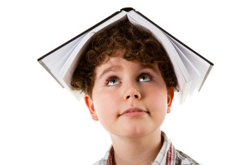 Boy with book on head isolated on white background