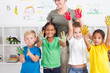 preschool kids with paint on hands with teacher