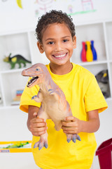 happy indian boy holding plastic dinosaur