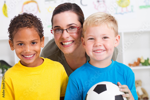 happy preschool teacher with two boys in classroom