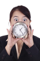 Asian businesswoman shocked holding a table clock