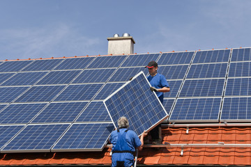 Two workmen are mounting solar