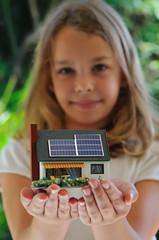 Fillette présentant une maison à énergie positive.