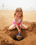 A Girl Digging at the Beach with a Blue Shovel