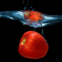 red apple dropped into water with splash isolated on black