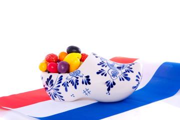 Old Dutch candy fruit in a Delft blue clog on a Dutch Flag isola