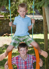 Portrait of two young brothers on a garden swing