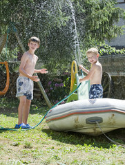 Two Young Boys playing in the garden with a hosepipe