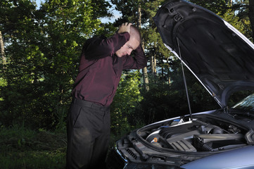 man having car problems in forest