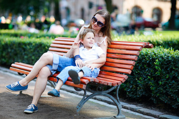Mother and son sitting on bench in park