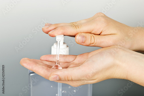 Leinwandbild Motiv Hands applying sanitizer gel