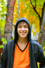 smiling teenager stand in the autumn park