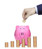 Person inserting a coin into a  pink piggy bank with stack of co poster