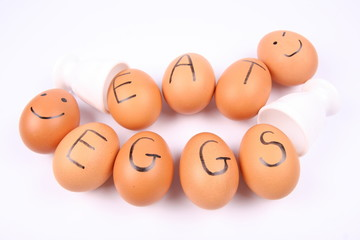 Eggs with an inscription EAT EGGS and some with smiling faces
