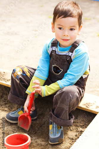 little boy playing in the sandbox